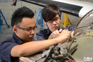 Nilai's Diploma in Aircraft Maintenance students working on the airplane in the hangar on the university's campus.