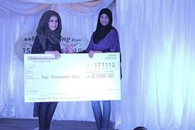 UCSI fashion student Worood Abdul Karim posing with her mock cheque of RM2,000 and ICAD head (fashion department) Nur Mashita bt Kamalun Ariffin posing during the bridal competition cum exhibition, themed, 'Victorian High Tea Time'.
