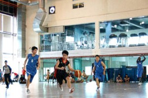 UCSI University students playing basketball at the Multipurpose Hall with the Gym in the background.